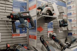 Display stand of Bosch power tools including drills, sander, and jigsaw.
