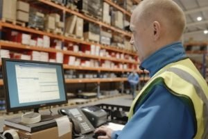 Blonde-haired man in hi-vis jacket using computer in warehouse.