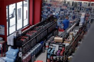 Man organizing car oils and car lubricants in HBA Powerstore shop.