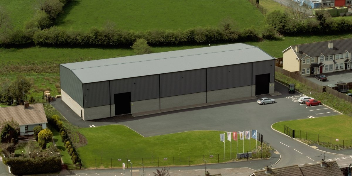 Overhead shot of large distribution centre building with surrounding grass areas and homes.
