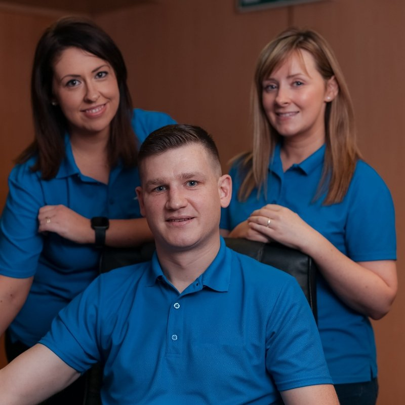 Two young women and one young man in blue staff uniform.