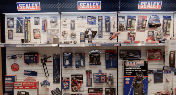 Display stand of Sealey tools including pressure washer, socket set, and grinding discs.